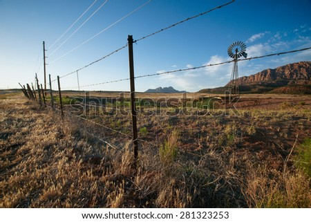 Barbed wire fence marks the edge of ranchland in the dry desert of Utah. - stock photo