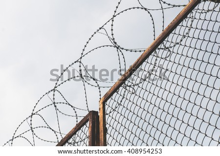 Barbed wire on a fence to provide security  - stock photo