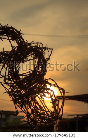 Barbed wire silhouette on sunset sky - stock photo