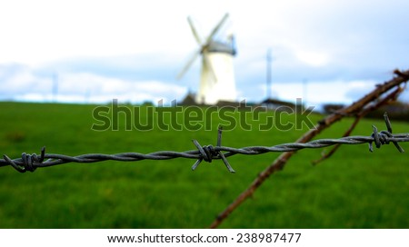 Barbed wire with windmill in Northern Ireland - stock photo