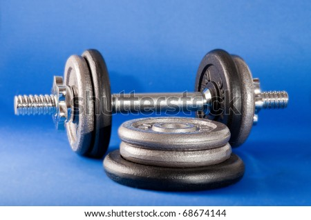 Barbell with free weights on a blue background - stock photo