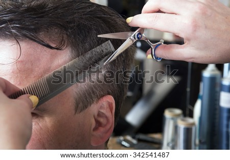 Barber cuts hair of handsome satisfied client in professional  hairdressing salon. - stock photo