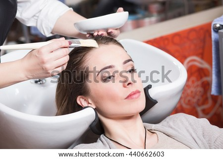 Barber girl combing her hair in beauty saloon. Beautiful lady having her hair washed by hairdresser in hairdressing saloon. - stock photo