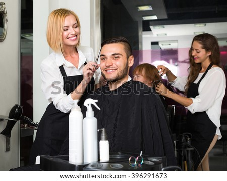 Barber makes the cut for young man in the barbershop - stock photo