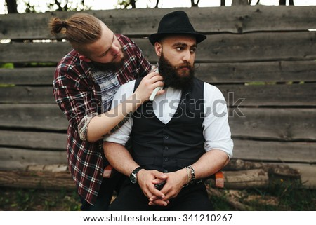 barber shaves a bearded man Outdoors - stock photo