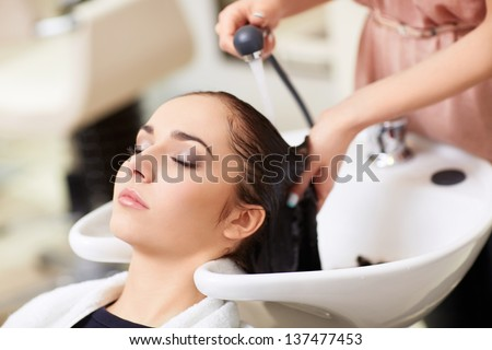 Barber washes the girl's head in the barbershop - stock photo