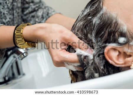 Barber washes the girl's head in the barbershop. - stock photo