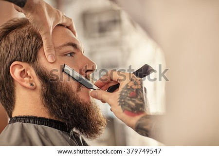 Barber with old-fashioned black razor shaving bearded man  - stock photo