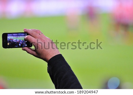 BARCELONA - APR 21: A supporter of F.C. Barcelona football team, recording a goal with his mobile phone camera at the Camp Nou Stadium on April 21, 2014 in Barcelona, Spain. - stock photo