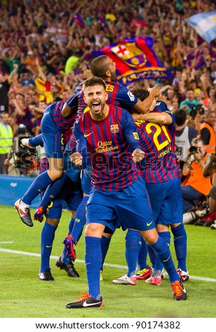 BARCELONA - AUGUST 17: Gerard Pique celebrates the goal of Leo Messi during the Spanish Super Cup final match between FC Barcelona & Real Madrid, 3 - 2, on August 17, 2011 in Barcelona, Spain. - stock photo