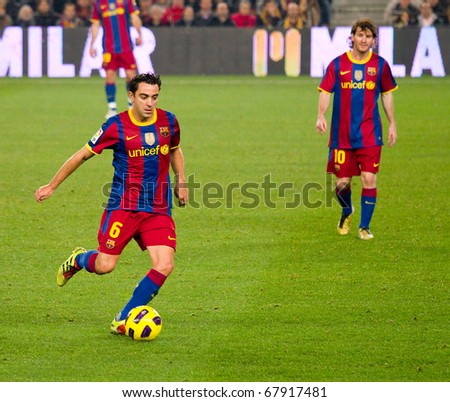 BARCELONA - DECEMBER 13: Nou Camp stadium, Spanish Soccer League: FC Barcelona - Real Sociedad, 5 - 0. In the picture, Xavi Hernandez (left) in action. December 13, 2010 in Barcelona (Spain). - stock photo