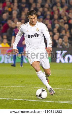 BARCELONA - JANUARY 25: Cristiano Ronaldo of Madrid in dribbling action during the Spanish Cup match between FC Barcelona and Real Madrid, final score 2 - 2, on January 25, 2012, in Barcelona, Spain. - stock photo