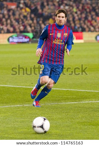 BARCELONA - JANUARY 25: Lionel Messi in action at the Spanish Cup match between FC Barcelona and Real Madrid, final score 2 - 2, on January 25, 2012, in Camp Nou, Barcelona, Spain. - stock photo