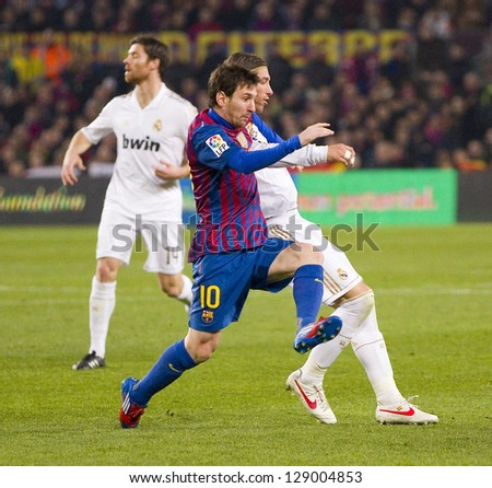 BARCELONA - JANUARY 25: Lionel Messi (middle) of FCB in action at the Spanish Cup match between FC Barcelona and Real Madrid, final score 2 - 2, on January 25, 2012, in Barcelona, Spain. - stock photo