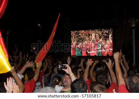 BARCELONA - JULY 11: Spanish supporters watching the match Spain - Holland in a giant screen and celebrating the victory of the World Cup 2010. July 11, 2010 in El Masnou (Barcelona, Spain). - stock photo