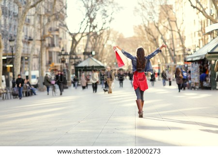 Barcelona, La Rambla shopping woman. Female shopper walking happy away with shopping bags raised up. From the famous landmark street in Catalonia, Spain. - stock photo