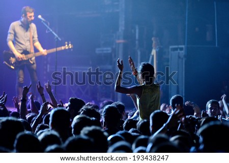 BARCELONA - MAY 16: A girl (fan) from the audience clapping and screaming in front of his favourite guitarist in a concert at Razzmatazz discotheque on May 16, 2014 in Barcelona, Spain. - stock photo