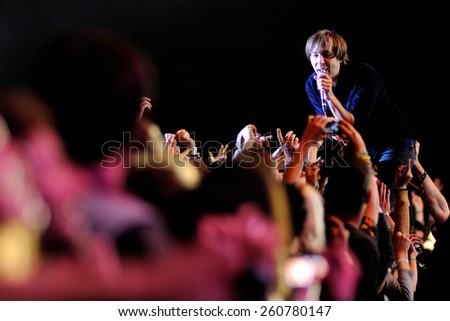 BARCELONA - MAY 23: Frontman of Phoenix (band) singing surrounded by the audience performs at Heineken Primavera Sound 2013 Festival on May 23, 2013 in Barcelona, Spain. - stock photo