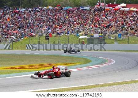 BARCELONA - MAY 13: Some cars racing at the race of Formula One Spanish Grand Prix at Catalunya circuit, on May 13, 2012 in Barcelona, Spain. The winner was Pastor Maldonado of Williams Renault team. - stock photo