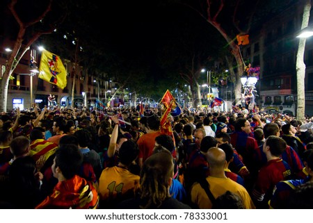 BARCELONA - MAY 11: Some supporters of FC Barcelona celebrate the Spanish League Championship victory in Catalunya square, Canaletes fountain and Rambla street, on May 11, 2011 in Barcelona, Spain. - stock photo
