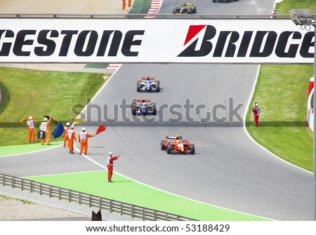 BARCELONA - MAY 9: The support personnel waves flags to finishing bolides of stage of race GP2 on may 9, 2010  in Barcelona, Spain - stock photo