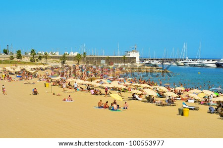 BARCELONA, SPAIN - AUGUST 16: Barceloneta-Somorrostro Beach on August 16, 2011 in Barcelona, Spain. This beach, 522 meters long, hosts about 400,000 visitors during the summer season - stock photo