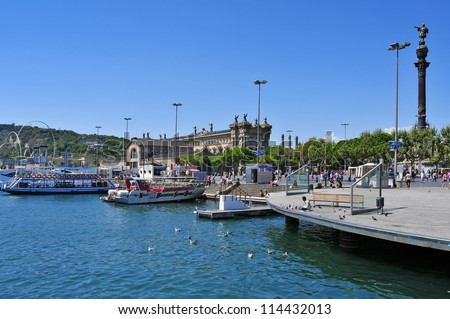 BARCELONA, SPAIN - AUGUST 16: Port Vell and Columbus Monument on August 16, 2012 in Barcelona, Spain. The monument is a 60 meters tall structure in honor of Columbus at the end of La Rambla - stock photo
