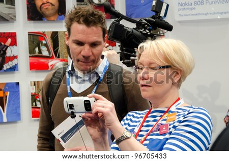 BARCELONA, SPAIN - FEB 26: Nokia employee demonstrates the Nokia 808 PureView prototype at the GSMA MWC 2012 Nokia stand on Feb 26, 2012 in Barcelona, Spain - stock photo
