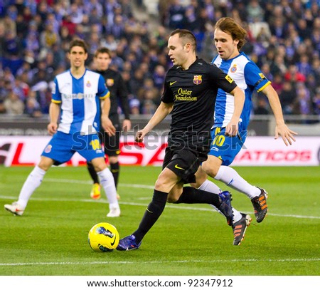 BARCELONA, SPAIN - JANUARY 8: Andres Iniesta (M) of Barcelona in action during the Spanish league match between RCD Espanyol and FC Barcelona, final score 1-1, on January 8, 2012, in Barcelona, Spain. - stock photo