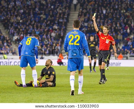 BARCELONA, SPAIN - JANUARY 8: Referee giving yellow card during the Spanish league match between RCD Espanyol and FC Barcelona, final score 1-1, on January 8, 2012, in Barcelona, Spain. - stock photo