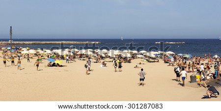 BARCELONA, SPAIN - JULY 4, 2015: A crowd of bathers in La Barceloneta Beach in Barcelona, Spain. This popular beach hosts about 500,000 visitors from everywhere during the summer season. - stock photo