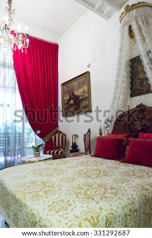BARCELONA, SPAIN, JULY 16: Classical and traditional luxury hotel room in Barcelona with red curtains and pillows. Spain 2012 - stock photo