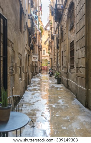 BARCELONA, SPAIN - JUNE 30. Narrow streets and alleys in the Barcelona district El Raval. There are lots of shops and coffee shops in the neighborhood. El Raval is located in the old part of Barcelona - stock photo