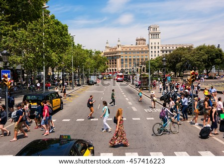 BARCELONA, SPAIN - JUNE 6, 2016:  People fill the busy Catalonia Square in Barcelona.The plaza covers an area of about 50,000 square meters. It is especially known for its fountains and statues.  - stock photo