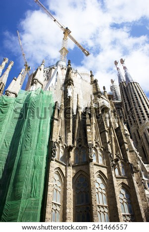 BARCELONA, SPAIN - JUNE 30, 2013: The Basilica of La Sagrada Familia against blue sky. Designed by Antoni Gaudi, its construction began in 1882 and is not finished yet.  - stock photo
