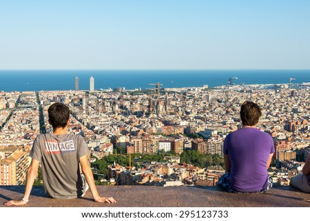 BARCELONA, SPAIN - JUNE 29. Young people are watching the skyline of Barcelona on June 29, 2015. The district Poblenou. The Sagrada Familia, the Towers of Port Olimpic and the harbor in Barcelona - stock photo