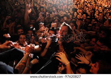 BARCELONA, SPAIN - MARCH 13: Pierre Bouvier, singer of Simple Plan band, surrounded by his fans, performs at Razzmatazz on March 13, 2012 in Barcelona, Spain. - stock photo