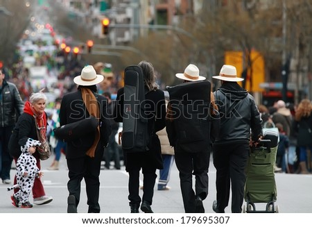 BARCELONA, SPAIN - MARCH 1: Unidentified musicians walking in the middle of Sants Street before carnival parade begin on March 1, 2014 in Barcelona, Spain. - stock photo