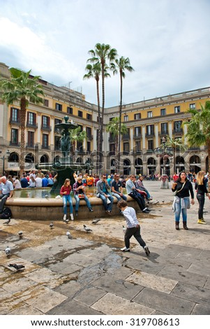 BARCELONA, SPAIN - MAY 02: Groups of Tourists Gathered Around Central Water Fountain in Placa Reial, a Popular Tourist Destination in Barcelona, Spain - stock photo