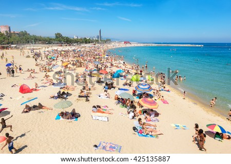 BARCELONA, SPAIN- MAY 27, 2015: Many people sunbathing and having fun on the beach in Barcelona, Spain. Port Olimpica, one of the popular beaches of the Mediterranean coast - stock photo