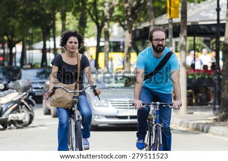BARCELONA, SPAIN - OCTOBER 7, 2014: A couple, riding a bike, driven on one of the busiest streets of the city, next to a city bus stand. - stock photo