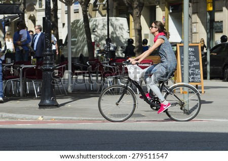 BARCELONA, SPAIN - OCTOBER 6, 2014: A young woman riding her bicycle, stroll along one of the busiest streets of the city, next to a city bus stand. - stock photo