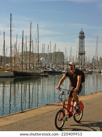 BARCELONA, SPAIN - SEPTEMBER 19, 2014. Coastal zone and the port, view of the port in Barcelona. Man  riding on bikes. - stock photo