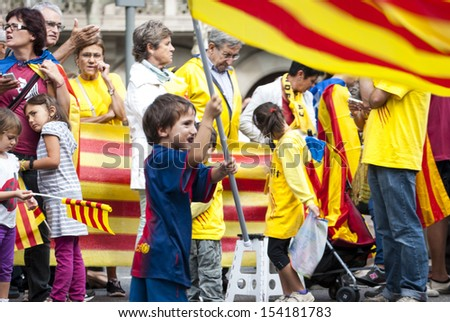 """BARCELONA, SPAIN - SEPTEMBER 11:Unidentified kids waving flags during """"Catalan Way"""", silent demonstration for independent Catalonia in Barcelona, Spain on September 11, 2013 - stock photo"""