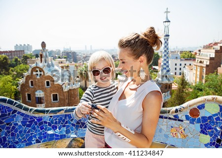 Barcelona will show you how to remarkably spend holiday. Happy mother and baby checking photos in digital camera at Park Guell - stock photo