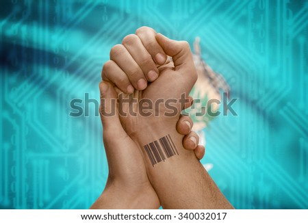 Barcode ID number tattoo on wrist of dark skinned person and USA states flag on background - Oklahoma - stock photo