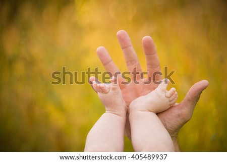 Bare feet of a cute baby on the summer background. Childhood in the farm. Small bare feet of a little baby girl. Mother holding baby feet. - stock photo
