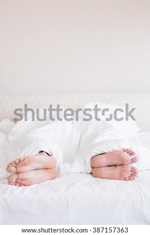 Bare feet of gay couple out from the blanket in bed - stock photo