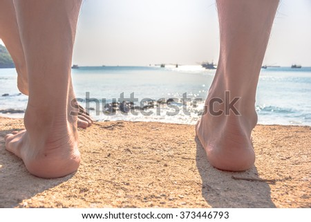 bare feet walking at a beach at sunset, with a wave's edge foaming gently beneath them, toned colors - stock photo