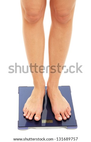 Bare female feet standing on scale isolated on white - stock photo